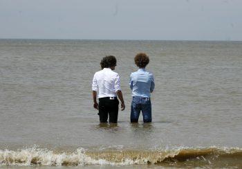 Mannen staan in de zee met overhemd van Ceesnco